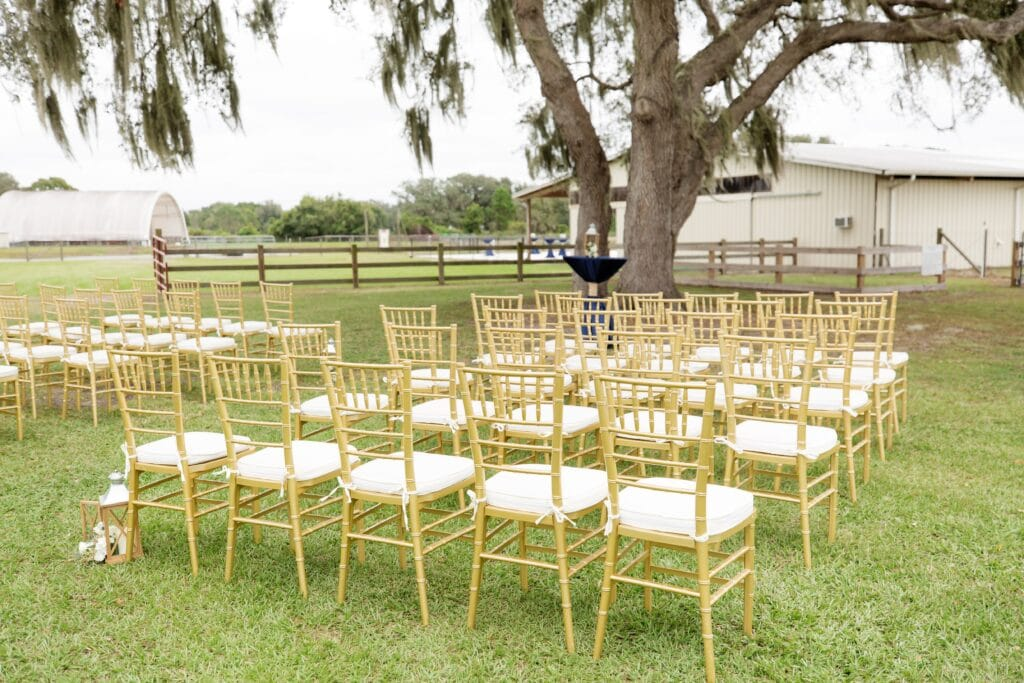 rows of gold and white chairs set up for outdoor wedding ceremony on farm